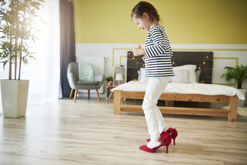 Little girl dressing up, wearing mother's red high heels - ABIF01174