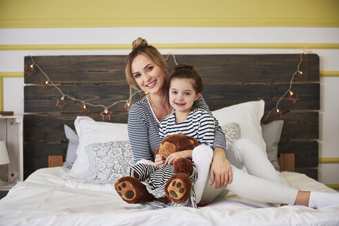 Mother and daighter sitting on bed, girl honding teddy bear - ABIF01180