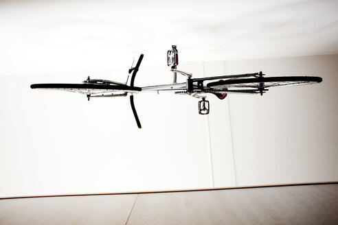Low angle view of bicycle hanging from ceiling - ASTF04893