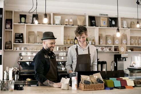 Smiling male baristas working at counter in coffee shop - ASTF04956
