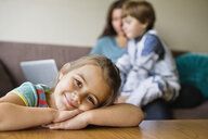 Portrait of happy girl leaning on coffee table with mother and brother sitting in living room at home - ASTF05046