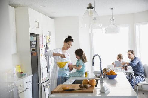 Mother pouring orange juice for daughter morning kitchen - HEROF24548