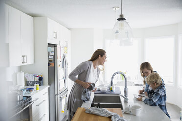 Mother drying dishes watching children using digital tablet - HEROF24557