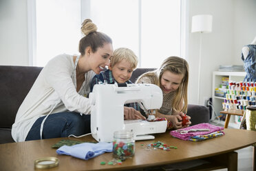 Mother and children sewing at sewing machine - HEROF24563