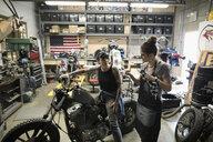 Female motorcycle mechanics talking, fixing motorcycle in auto repair shop - HEROF24626