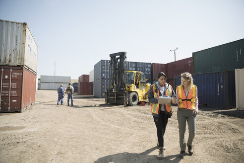 Female workers with coffee and clipboard walking in sunny industrial container yard - HEROF24650
