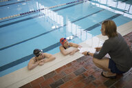 Female coach talking to swimmers in swimming pool at practice - HEROF24665