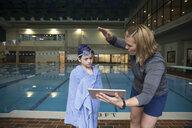 Female coach with digital tablet coaching girl swimmer wrapped in towel at swimming pool practice - HEROF24674