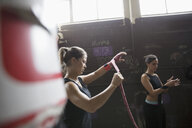 Fit female boxers wrapping wrists behind punching bags in gritty gym - HEROF24695