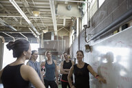 Female instructor and crossfit students at whiteboard in gym - HEROF24698