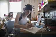 Female college student with headphones studying at desk in dorm room - HEROF24716