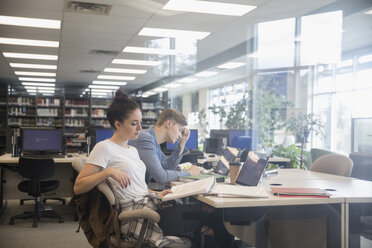 Female college student studying, researching at laptop in library - HEROF24758