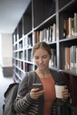 Female college student drinking coffee and texting with cell phone at bookshelf in library - HEROF24767