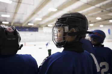 Focused, serious boy ice hockey player in helmet watching game - HEROF24779