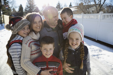 Family hugging on sunny snowy street - HEROF24782
