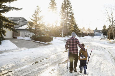 Father and son walking with ice hockey sticks and ice skates on snowy road - HEROF24788