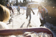 Families playing ice hockey in sunny, snowy driveway - HEROF24794
