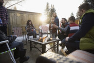Families, neighbors roasting marshmallows at fire pit in driveway - HEROF24797