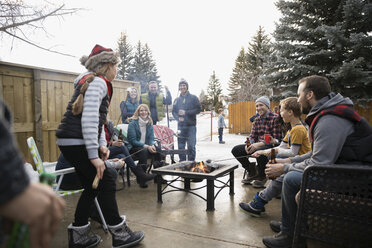 Families, neighbors roasting marshmallows and drinking beer at fire pit in snowy driveway - HEROF24800
