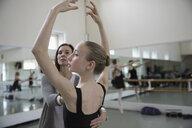 Female instructor adjusting posture of teenager ballet dancer practicing in dance studio - HEROF24836