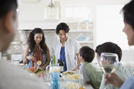 Family eating and drinking in beach house kitchen - HEROF24890