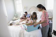 Family packing for vacation on bed - HEROF24896