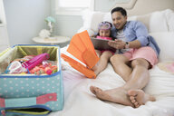 Father and daughter wearing flippers packing for vacation, using digital tablet on bed - HEROF24899