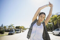 Female Latina runner stretching arms on sunny road - HEROF24908