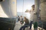 Friends opening bottle of champagne on sunny sailboat - HEROF24917