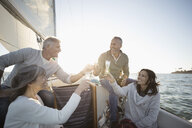 Friends toasting champagne flutes on sunny sailboat - HEROF24920