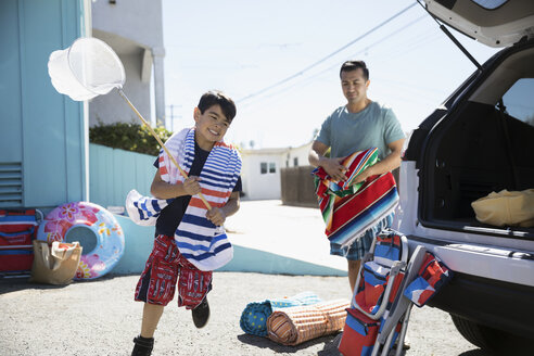 Father and son loading car for beach trip in sunny driveway - HEROF24929