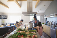 Family cooking vegetables in kitchen - HEROF24944