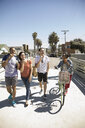 Friends walking and eating ice cream cones on sunny California sidewalk - HEROF24953