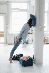 Jet-legged woman leaning on pillar - KNSF05608