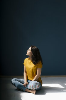 Woman sitting cross-legged in sunlight, with eyes closed - KNSF05611