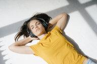 Woman lying on floor, relaxing in the sunlight, listenng music - KNSF05632