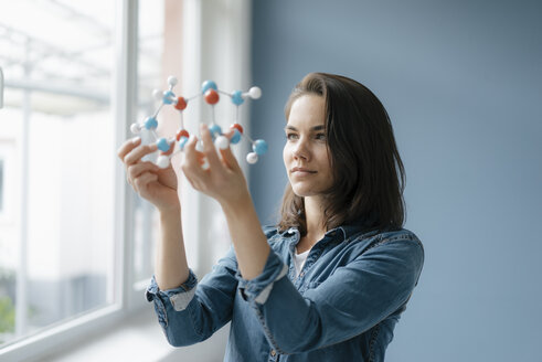 Female scientist studying molecule model, looking for solutions - KNSF05644