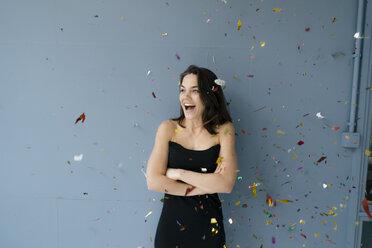 Happy woman watching flying confetti - KNSF05659