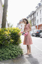 Woman watering plants with a flamingo can in an urban street - KNSF05695