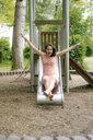 Woman sliding on a slide on a playground - KNSF05704