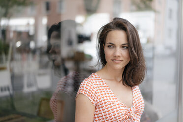 Portrait of a pretty woman, standing in front of window display - KNSF05707