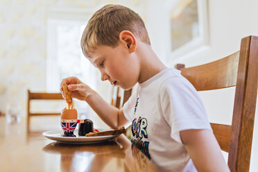 UK, sad boy sitting at breakfast table eating boiled egg - NMS00302