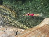 Switzerland, Ticino, Verzasca Valley, Val Versazca, woman swimming in refreshing Verzasca river - GWF05902