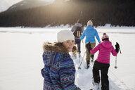 Family snowshoeing in snowy field - HEROF25016