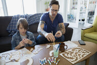 Father and son assembling and painting craft model - HEROF25076