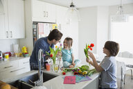 Father and children arranging tulip bouquet in kitchen - HEROF25079