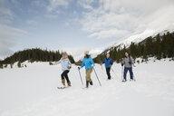 Couples snowshoeing in snowy field - HEROF25121