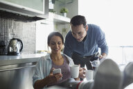 Couple drinking coffee and texting in kitchen - HEROF25208