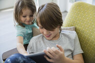 Brother and sister sharing digital tablet - HEROF25316