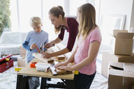 Children watching mother hammer nail into wood trim - HEROF25319
